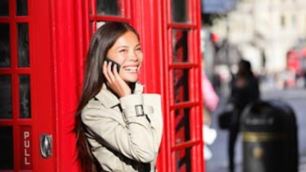Woman outside an old red telephone box