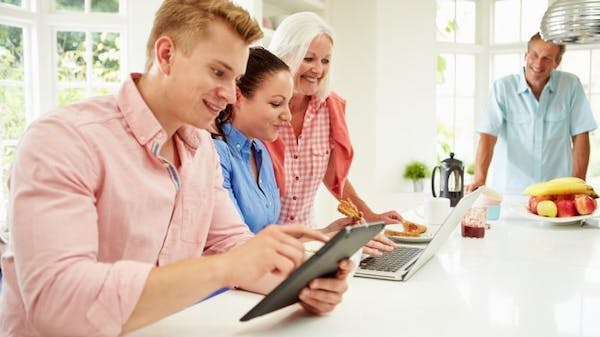 Family using dual laptops in the kitchen