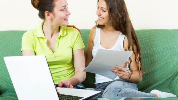 Young women using a laptop on a sofa